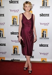 Carey Mulligan stuck to jewel tones in navy Roger Vivier Epine pumps. She wore the satin platforms with a burgundy cocktail dress and clutch.