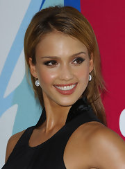 Jessica Alba paired her sleek updo hairstyle with diamond drop earrings.