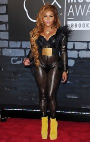 Lil Kim chose a bold fitted jumpsuit with feathered shoulder pads and a wide belt for her figure-hugging look at the 2013 VMAs.