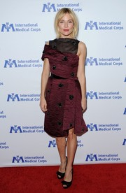 Sienna Miller paired her dress with bow-adorned black peep-toe pumps.