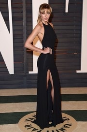Jessica Hart flaunted her supermodel figure in a slinky black halter gown with a thigh-high slit during the Vanity Fair Oscar party.