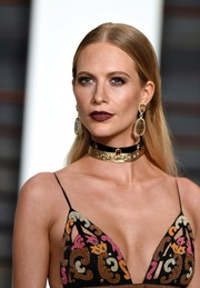 Poppy Delevingne wore her hair loose and slicked down with a center part during the Vanity Fair Oscar party.