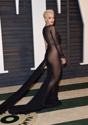 Rita Ora opted for a bold look at the Vanity Fair Oscar Party in a figure-hugging gown with a sheer panel along one side.