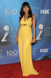 She adds a great finishing touch to her canary yellow dress with a gold clutch.
