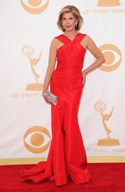 Christine looked red-hot in a fitted red evening gown with thick V-neck straps and a long train.