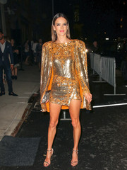 Alessandra Ambrosio completed her high-shine look with gold sandals by Nicholas Kirkwood.