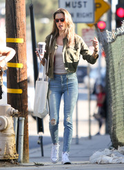 Alessandra Ambrosio layered a cropped army jacket over a striped shirt for a day out in LA.