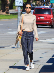 Alessandra Ambrosio headed out in LA wearing a beige Zoe Jordan mock-neck sweater with slit sleeves and a fringed hem.