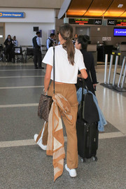 Alessandra Ambrosio accessorized with a tan and white scarf to match her pants while catching a flight.