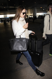 Alessandra Ambrosio stayed comfy in skinny jeans and a ribbed sweater for a flight out of LAX.