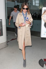 Alexa Chung layered a beige trenchcoat over a denim romper for her airport look.