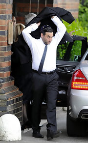 Alex Winehouse, Amy Winehouse's broter, attends her funeral in a narrow blue tie.