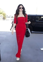 Andrea Riseborough looked lovely in red when she flew from LAX sporting this red gown with a nude illusion yoke and panels.