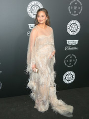 Chrissy Teigen complemented her dress with an elegant Jimmy Choo tube clutch.