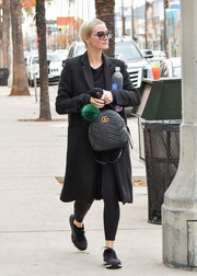 Ashlee Simpson's arm candy for the day was a black Gucci Marmont quilted backpack.