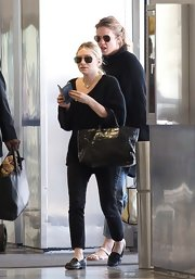 Ashley Olsen kept her travel look monochromatic with this black V-neck sweater paired over black jeans.