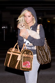 Ashley holds her pooch close while arriving from LAX. She went low key in her hooded sweat shirt and sweats, but dresses things up with a hefty shoulder bag.