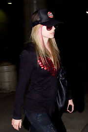 Avril wears one of her signature mesh trucker caps with her black zip-up hoodie.