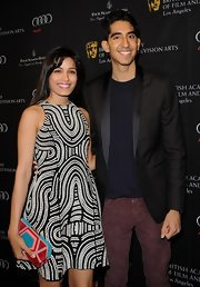 The actress mixed patterns, pairing her graphic black and white dress with a colorful paneled clutch.
