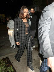 Bella Hadid teamed a black-and-white plaid suit by Dior with a sexy see-through top for a night out in LA.