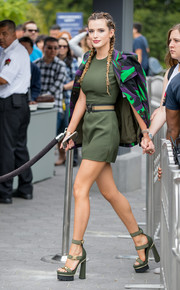 Bella Thorne teetered sexily on a pair of army-green triple-strap platform sandals, also by Versace.