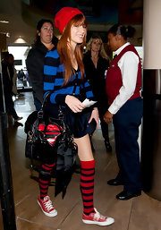 Bella Thorne was mad about stripes at LAX in a blue and black rugby striped cardigan accessorized by contrasting knee high socks.