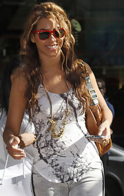 Beyonce adds a burst of color to her outfit with these retro red plastic wayfarers.