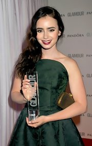 Lily Collins paired a studded clutch with a green strapless dress, both by Alexander McQueen, for the Glamour Women of the Year party.