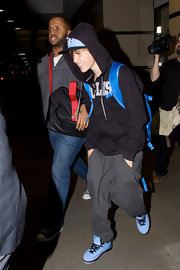 Justin makes his laid back airport outfit pop with a pair of baby blue sneakers.