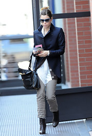 Jessica looks chic in a navy shoulder padded blazer, khakis and a pair of brown leather ankle boot wedges.
