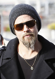 Brad's sunglasses are good for a casual outfit. They have a flat gold frame with a solid true brown lens.