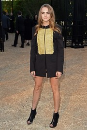 Cara Delevingne teamed her jacket with black open-toe lace-up booties by Burberry.