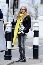 Cara Delevingne rocked a cable knit scarf in a cool neon yellow color while modeling in London.