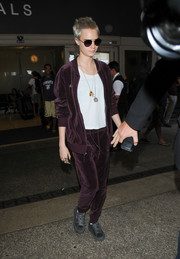 Cara Delevingne kept it laid-back and sporty in a plum velour track jacket by Puma during a flight to LAX.