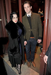 Dita wears a dramatic fur trimmed black coat with her retro ensemble while out in Paris during Fashion Week.