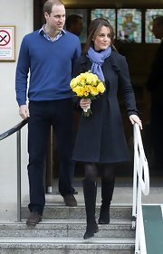Kate Middleton left the hospital bundled up in a navy plaid wool topper and knee-high boots.
