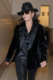 Catherine Zeta-Jones looked glam with this black fedora and sunnies combo while catching a flight.