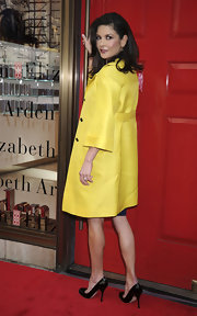 Black patent stilettos are a simple but sexy complement to this yellow coat.