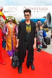 Adam Lambert chose a flowing cardigan for his rocker cool look while flying into Austria.