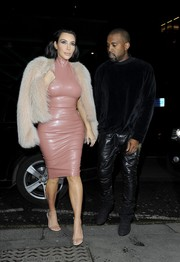 Kim Kardashian layered a fur jacket over her latex dress for a more glamorous finish.