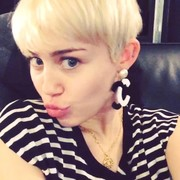 Miley Cyrus coordinated her black-and-white striped outfit with a pair of dangling CC earrings by Chanel for this social media pic.