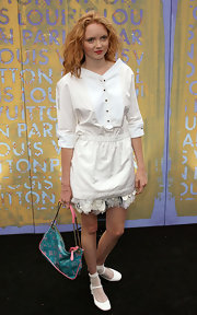 Lily Cole added a dose of color to her all-white outfit with a blue and pink Louis Vuitton bag.