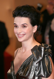 Juliette Binoche flashed a smile at the Cannes Film Festival as photographers took note of her chic bobby pinned updo.