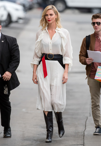 Charlize Theron paired her top with a matching pleated midi skirt.