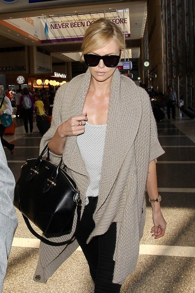 Charlize Theron topped off her travel ensemble with an elegant black leather tote by Alexander McQueen.