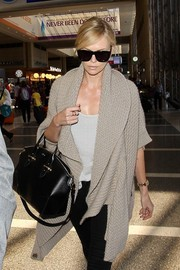 Charlize Theron hid her eyes behind a pair of oversized square shades by Karen Walker as she made her way through LAX.