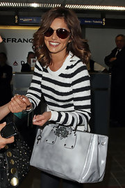 "Cheryl carried a chic grey leather tote bag with gunmetal colored hardware and a double top handle. The ""Spazzolato"" bag goes for $2,395 and features crystals and a detachable shoulder strap."