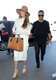 Chrissy Teigen caught a flight at LAX wearing a stylish long-sleeve white dress.
