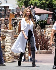 Chrissy Teigen visited 'Extra' wearing a cool white high-low wrap top.