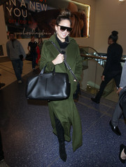 Chrissy Teigen looked cozy and stylish in a forest-green wool coat by Vatanika while catching a flight out of LAX.